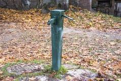 Old green antic water pomp. Autumn background in Kuldiga Latvia autumn background Stock Photo