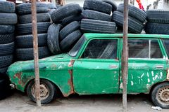 Old green Azerbaijani car in Baku, under a pile of tyres, from the side Royalty Free Stock Images