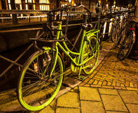 Old green bicycle parked near bridge in Amsterdam at night. Stock Photography
