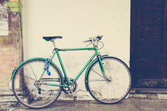 Old green bicycle at the wall Stock Photos