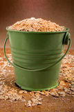 Old green bucket filled with oatmeal Royalty Free Stock Image