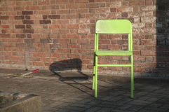 Old green chair next to an outdoor brick wall Stock Photography