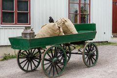 Old green colored horse carriage with wheels made of wood. Loaded with some old gunny sacks and a milk can. A crow sitting on top of the bag Stock Images