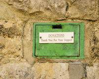 Old Green Donations Box Set in Stone Wall. Royalty Free Stock Image