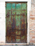 Old green door and brick wall. Old wooden green door with peeling paint and rusting hinges in an ancient brick wall Stock Photography