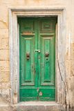 Old green door with lion`s head knockers stock images