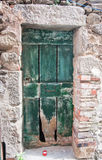 Old green door in stone wall. Royalty Free Stock Images