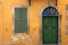 Old green door and window of ancient yellow building Royalty Free Stock Photography
