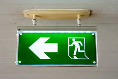 Old Green fire exit sign at hotel. Royalty Free Stock Photos