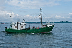 Old Green Fishboat. Old steel fish cutter sailing with photographers outside Gdynia harbour, Poland Stock Photo