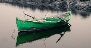 Old green fishing boat on black and white background. Old green fishing rowing boat on black and white background Royalty Free Stock Image