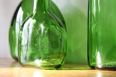 Old green glass bottles. Three old green glass bottles over wooden surface. Closeup, daylight Stock Photo