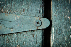 Old Green Hinge. Detailed old worn green hinge affixed to a wooden door or shutter. On close inspection you can see the presence of mites royalty free stock photos