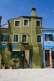 The old green house on Burano island, Veneto region, Italy. Stands at the end of the water canal street Royalty Free Stock Image