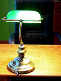 Old green lamp. Close up of the retro style lamp on the wooden desk and black armchair. Home office area Stock Photography