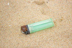 Old green lighter in sand Stock Photos