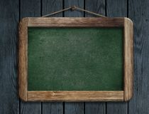 Old green menu blackboard hanging on wooden wall Stock Photos