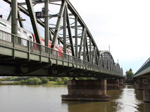 Old Green Metal Railroad Bridge with Red Train Crossing River Stock Image