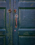Old green painted wooden door with iron rusty handle. Stock Photography