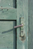 Old green painted wooden door and a rusty doorknob Royalty Free Stock Photo