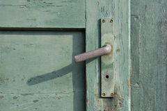 Old green painted wooden door and a rusty doorknob Stock Image