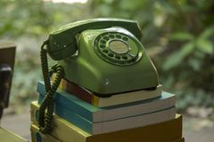 Old green phone Put on the book royalty free stock image