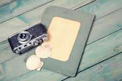 Old green photo frame with two sea shells and vintage camera Stock Photos