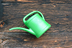 Old green plastic watering can hang on wooden wall. Old green plastic watering can hang on dark brown wooden wall royalty free stock image