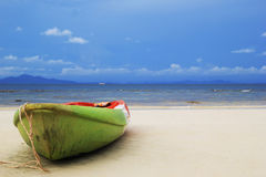 The old green-red-white boat on the sand beach with sea and a mountain and blue sky on background. Stock Photos