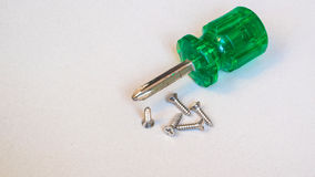 Old green screw driver and matal screw Royalty Free Stock Photo