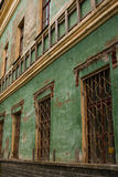 Old green shabby wall of an abandoned building Stock Photos