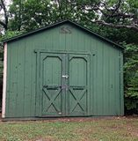 Old green shed. Old weathered green shed with double doors Stock Image