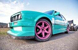 Old green sport car with pink wheels Royalty Free Stock Image