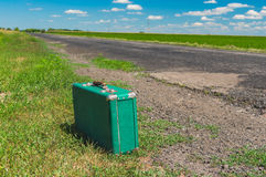 Old green suitcase hiking on a country road Royalty Free Stock Photos