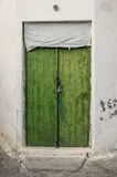 Old green timber door in the scuffed wall Royalty Free Stock Photos