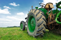 Old green tractor in the field royalty free stock photo
