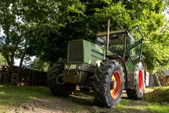 Old green tractor under a tree on a farm, selected focus, narrow Stock Photo