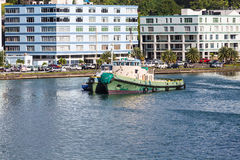 Old Green Tugboat By Modern Buildings Royalty Free Stock Photos