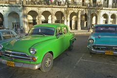 Old green and turquoise American cars are parked in front of old buildings in Old Havana, Cuba Royalty Free Stock Images