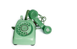 An old green vintage rotary style telephone off the hook. An old black vintage rotary style telephone off the hook isolated over a white background with clipping Stock Photos