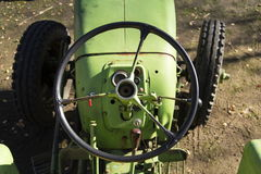 Old green vintage tractor stands on farm yard Stock Photo