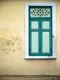 Old green window. Old green closed window on yellow wall Royalty Free Stock Photography