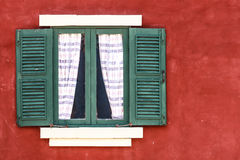 Old Green Window with Curtain on Red Wall,  Right Copy Space. Old Green Window with Curtain on Red Wall,  Copy Space on Right Stock Photo