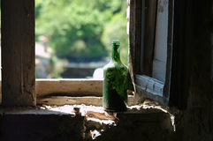 Old green wine bottle in window Stock Photography