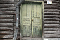 The old green wood door of old log house and water drain Stock Photo