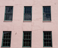 Green Windows in Pink Stucco. Old green wood windows in a pink stucco wall Royalty Free Stock Images