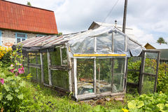 Old greenhouse for growing vegetables made from discarded materi Stock Photos