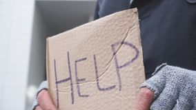 Old grey bearded man standing with sign HELP, asking for money, food, shelter.