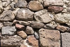 Old grey and brown rough stone wall, closeup texture background, selective focus, shallow DOF Stock Image