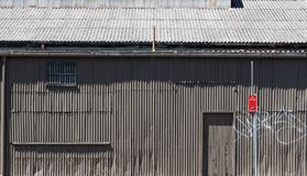 Old Grey Corrugated Iron Building. A battered old dark grey, stealth colours, corrugated iron or steel industrial building stock photos